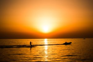 silhouette photo of man riding a motorboat with man surfboarding behind during golden hour