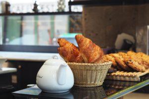white ceramic teapot beside brown wicker basket on table