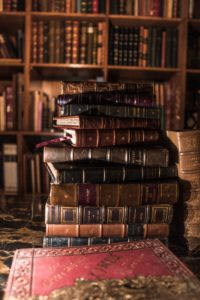 stack of books on brown wooden shelf