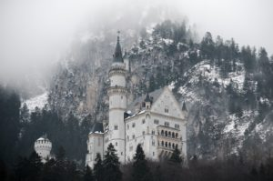 white concrete castle below mountain covered with tree during daytime